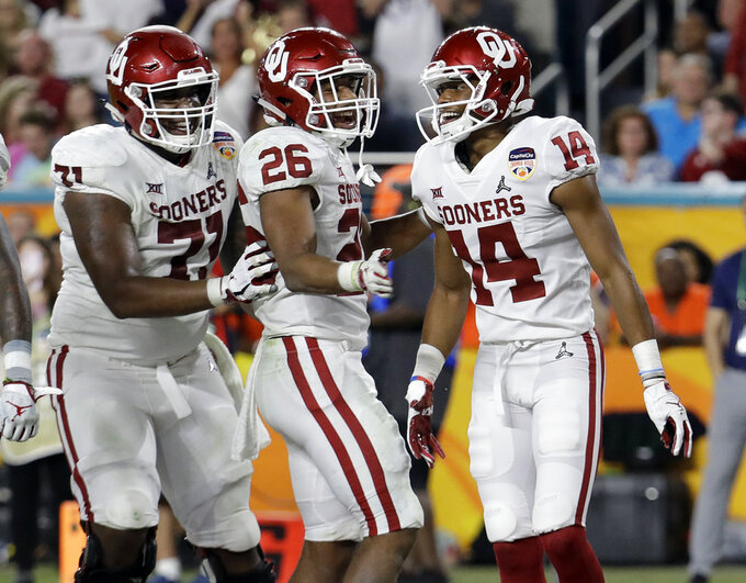 Oklahoma offensive lineman Bobby Evans (71) and running back Kennedy Brooks (26) congratulate wide receiver Charleston Rambo (14), after Rambo scored a touchdown, during the second half of the Orange Bowl NCAA college football game against Alabama, Saturday, Dec. 29, 2018, in Miami Gardens, Fla. (AP Photo/Lynne Sladky)