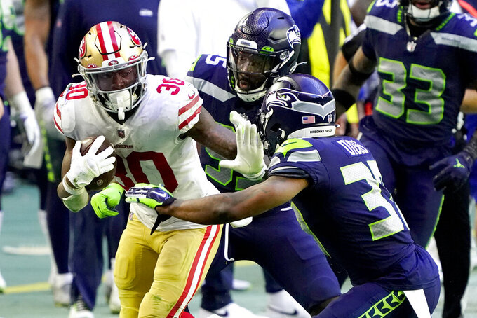 San Francisco 49ers running back Jeff Wilson (30) tries to avoid Seattle Seahawks free safety Quandre Diggs during the second half of an NFL football game, Sunday, Jan. 3, 2021, in Glendale, Ariz. (AP Photo/Rick Scuteri)