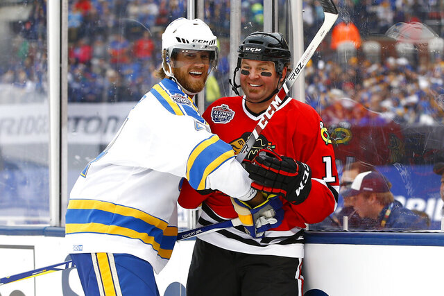 FILE - In this Dec. 31, 2016, file photo, former St. Louis Blues' Chris Pronger, left, laughs with former Chicago Blackhawks' Kyle Calder after a check during the Winter Classic alumni outdoor hockey game at Busch Stadium in St. Louis. Pronger insists there's no ill will after his surprising split with the Florida Panthers earlier in July 2020. Pronger, who was senior vice president of hockey operations, just decided the time was right to step away from the game, even with the Panthers making a playoff push, he said. (AP Photo/Billy Hurst, File)