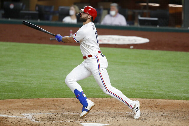 Texas Rangers' Joey Gallo follows through on a two-run home run that came off a pitch from Los Angeles Angels starter Patrick Sandoval in the sixth inning of a baseball game in Arlington, Texas, Saturday, Aug. 8, 2020. The Rangers' Todd Frazier scored on the hit. (AP Photo/Tony Gutierrez)