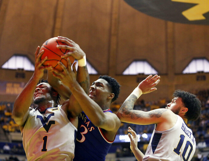 West Virginia forward Derek Culver (1) and Kansas forward David McCormack (33) fight for a rebound during the first half of an NCAA college basketball game Saturday, Jan. 19, 2019, in Morgantown, W.Va. (AP Photo/Raymond Thompson)