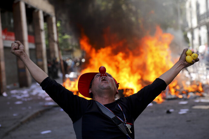 An anti-government demonstrator screams in font of a burning barricade in Santiago, Chile, Tuesday, Oct. 22, 2019. Protests in the country have spilled over into a fifth day, even after President Sebastian Pinera cancelled the subway fare hike that prompted rioting, arson and violent clashes that have almost paralyzed the country. (AP Photo/Rodrigo Abd)