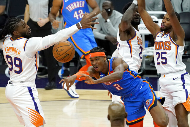 Oklahoma City Thunder guard Shai Gilgeous-Alexander (2) passes between Phoenix Suns forward Mikal Bridges (25), center Deandre Ayton (22) and forward Jae Crowder (99) during the first half of an NBA basketball game, Wednesday, Jan. 27, 2021, in Phoenix. (AP Photo/Matt York)