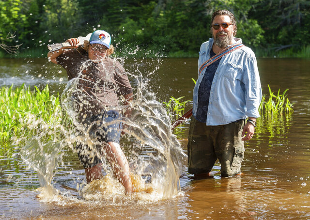 Karl Sundquist and his son Mikko pose and play in a river near his Cook, Minnesota home while promoting his new album