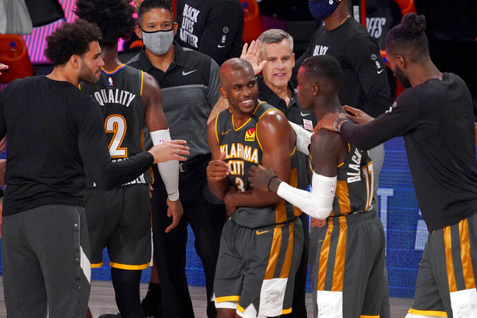 Oklahoma City Thunder's Chris Paul (3), Dennis Schroder (17), head coach Billy Donovan, center rear, and others celebrate their 104-100 win against the Houston Rockets in an NBA first-round playoff basketball game, Monday, Aug. 31, 2020, in Lake Buena Vista, Fla. (AP Photo/Mark J. Terrill)