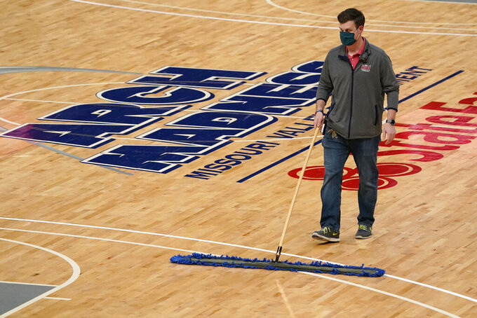 A worker cleans the court after it was announced that an NCAA college basketball game in the quarterfinal round of the Missouri Valley Conference men's tournament between Northern Iowa and Drake has been cancelled Friday, March 5, 2021, in St. Louis. (AP Photo/Jeff Roberson)