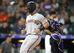 San Francisco Giants' Buster Posey scores the go-ahead run on a single by Alex Dickerson off Colorado Rockies relief pitcher Wade Davis during the 10th inning of a baseball game Tuesday, July 16, 2019, in Denver. The Giants won 8-4 in 10 innings. (AP Photo/David Zalubowski)