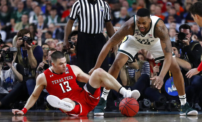 Texas Tech guard Matt Mooney, left, fights for a loose ball with Michigan State forward Nick Ward during the first half in the semifinals of the Final Four NCAA college basketball tournament, Saturday, April 6, 2019, in Minneapolis. (AP Photo/Jeff Roberson)