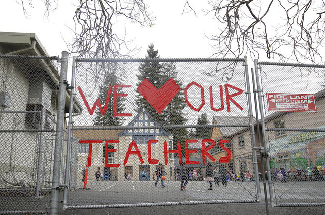 FILE - In this March 4, 2019, file photo, a sign supporting teachers is shown on a fence outside of Chabot Elementary School in Oakland, Calif. California Democratic Gov. Gavin Newsom presented a revised $203 billion budget proposal to state lawmakers Thursday, May 14, 2020, reflecting an economy and tax revenues hobbled by the coronavirus pandemic. . (AP Photo/Jeff Chiu, File)
