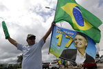 A demonstrator carries a Brazilian flag and a flag with an image of Brazil's President Jair Bolsonaro during a caravan celebrating Bolsonaro's 66th birthday, in Brasilia, Brazil, Sunday, March 21, 2021.  (AP Photo/Eraldo Peres)