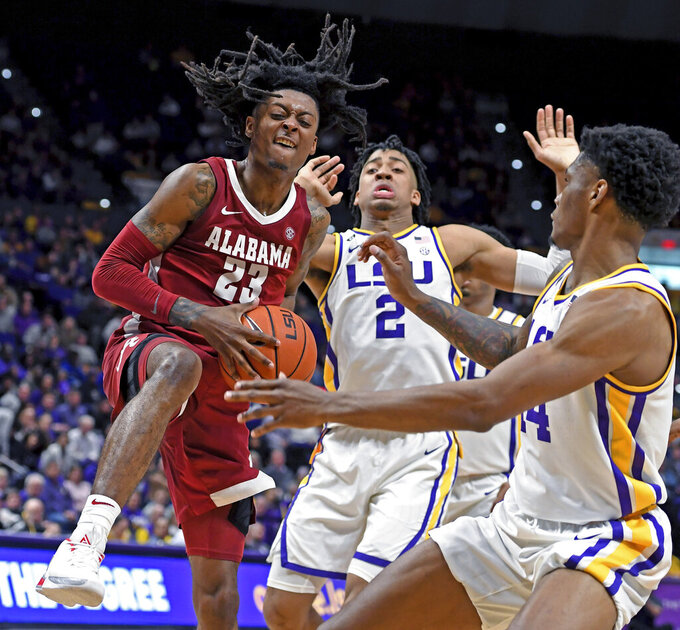 Alabama guard John Petty Jr. (23) comes down with the offensive rebound in front of LSU forward Trendon Watford (2) and LSU guard Marlon Taylor (14) during the second half of an NCAA college basketball game, Wednesday, Jan. 29, 2020, in Baton Rouge, La. LSU won 90-76. (AP Photo/Bill Feig)