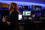 Erin Burke, left, Section Chief of the Child Exploitation Investigations Unit at Homeland Security, is interviewed inside the Victim Identification Lab, part of Homeland Security's Child Exploitation Investigations Unit, in Fairfax, Va., Friday, Nov. 22, 2019. The Homeland Security Investigations section's little-known Child Exploitation Investigations lab is where agents scour disturbing photos and videos of child sexual abuse.  They look for unlikely clues that help them identify the children and bring their abusers to justice. In one case, it was the loud, persistent chirping of a bird. Another time, it was unusual playground equipment. (AP Photo/Jacquelyn Martin)