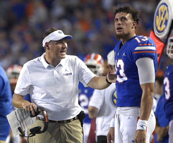 Florida head coach Dan Mullen, left, talks with quarterback Feleipe Franks (13) on the sideline during the first half of an NCAA college football game against Charleston Southern Saturday, Sept. 1, 2018, in Gainesville, Fla. (AP Photo/Phelan M. Ebenhack)
