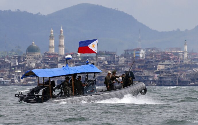 FILE - In this Oct. 19, 2017, file photo, Philippine Navy commandos aboard a gunboat patrol the periphery of Lake Lanao as smoke rises from the