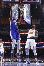 Philadelphia 76ers' Joel Embiid, left, goes up for the shot against New York Knicks' Julius Randle, right, during the first half of an NBA basketball game, Wednesday, Nov. 20, 2019, in Philadelphia. (AP Photo/Chris Szagola)