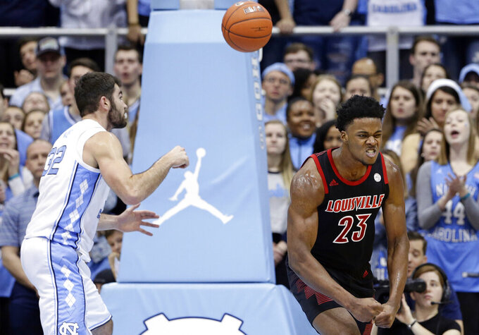 Louisville's Steven Enoch (23) reacts following a basket while North Carolina's Luke Maye reaches for the ball during the first half of an NCAA college basketball game in Chapel Hill, N.C., Saturday, Jan. 12, 2019. Louisville won 83-62. (AP Photo/Gerry Broome)