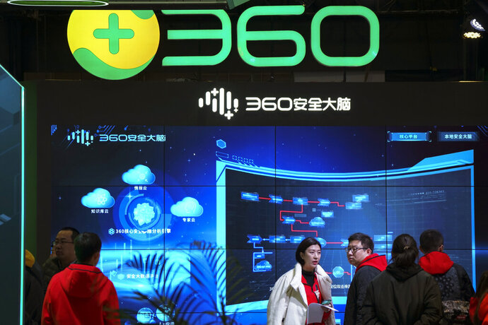 In this photo released by Xinhua News Agency, visitors tour the Chinese internet security firm Qihoo 360 showcasing it 5G digital security and protection system at the World 5G Convention in Beijing on Nov. 21, 2019. One of China's biggest tech companies has criticized the Trump administration for