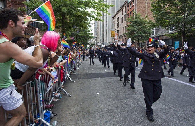 FILE - In this  Sunday, June 30, 2013 file photo, Members of the Gay Officers Action League of the New York police department are cheered during the gay pride march in New York. As Pride weekend approaches, the recent decision by organizers of New York City's event to ban LGBTQ police officers from marching in future parades while wearing their uniforms has put a spotlight on issues of identity and belonging, power and marginalization. (AP Photo/Craig Ruttle, File)
