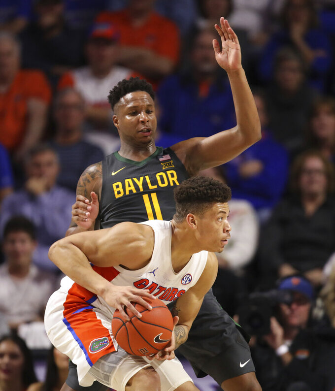 Baylor guard Mark Vital, top, defends against Florida forward Keyontae Johnson, bottom, during the second half of an NCAA college basketball game Saturday, Jan. 25, 2020, in Gainesville, Fla. (AP Photo/Matt Stamey)
