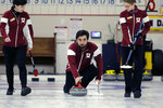 Harvard's Neekon Vafa, center, delivers a rock during the college curling national championship, Friday, March 8, 2019, in Wayland, Mass. (AP Photo/Bill Sikes)
