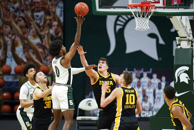 Michigan State forward Aaron Henry (0) shoots on Iowa center Luka Garza (55) in the first half of an NCAA college basketball game in East Lansing, Mich., Saturday, Feb. 13, 2021. (AP Photo/Paul Sancya)