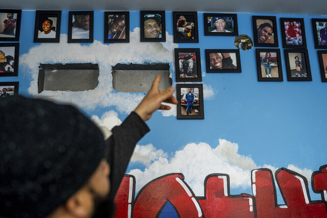 Darren Neal points to a wall of photographs of deceased community members, many of whom he knew, inside of the Truce Center in St. Paul, Minn., on Thursday, Jan. 9, 2020.  (Evan Frost/Minnesota Public Radio via AP)