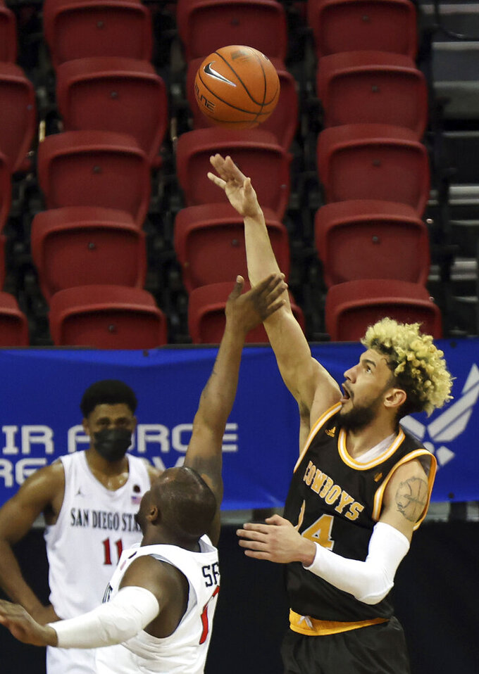 Wyoming guard Hunter Maldonado (24) shoots as San Diego State guard Adam Seiko (2) defends during the first half of an NCAA college basketball game in the quarterfinal round of the Mountain West Conference men's tournament Thursday, March 11, 2021, in Las Vegas. (AP Photo/Isaac Brekken)