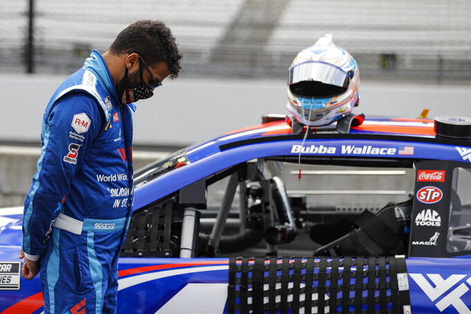 Bubba Wallace stands next to his car during a prayer before a NASCAR Cup Series auto race at Indianapolis Motor Speedway in Indianapolis, Sunday, July 5, 2020. (AP Photo/Darron Cummings)