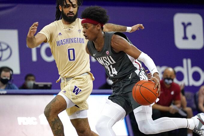 Washington State's Noah Williams (24) drives past Washington's Marcus Tsohonis in the first half of an NCAA college basketball game Sunday, Jan. 31, 2021, in Seattle. (AP Photo/Elaine Thompson)