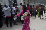 FILE - In this Friday, May 4, 2018 file photo, a woman walks with her baby as migrants and refugees wait outside the UNHCR offices for their papers inside the camp of Moria, Lesbos island, Greece. European governments breathed a sigh of relief as the European Union reached a deal with Turkey designed to stop hundreds of thousands of refugees and migrants heading into the heart of Europe. For many of those who had fled war, hunger and poverty hoping for a bright future on the continent, the deal shattered their dreams. (AP Photo/Petros Giannakouris, File)