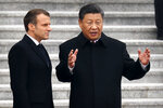 French President Emmanuel Macron, left, listens as Chinese President Xi Jinping talks during a welcome ceremony at the Great Hall of the People in Beijing, Wednesday, Nov. 6, 2019. (AP Photo/Mark Schiefelbein)