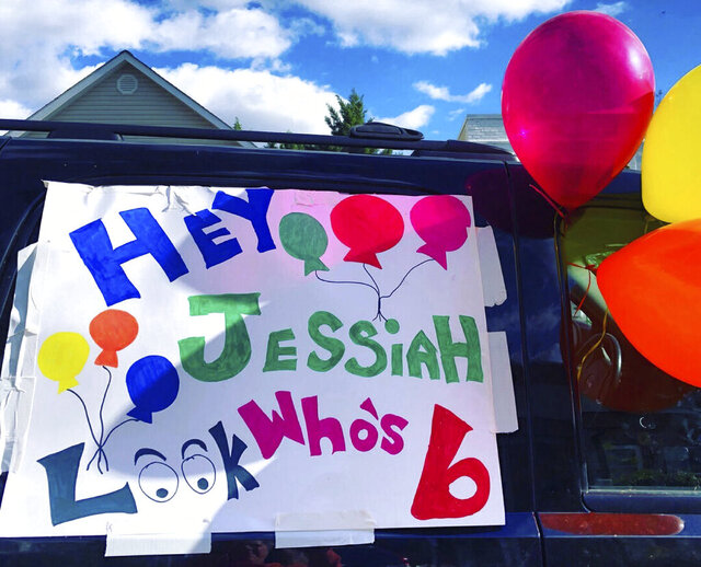 In this April 10, 2020, photo provided by Ashley Johnson, a birthday sign and a cluster of balloons hang on a car window ready for an impromptu, surprise birthday parade for 6-year-old Jessiah Lee, in Arlington, Va. After Jessiah's birthday party was upended due to the coronavirus, his close friend and mentor, Ashley Johnson, recruited the help of a local fire department, the police and dozens of neighbors to give him a birthday celebration. (Ashley Johnson via AP)