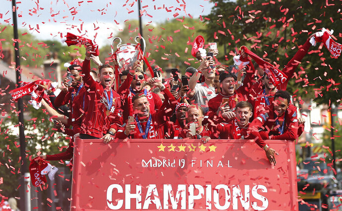 Liverpool soccer team ride an open top bus during the Champions League Cup Winners Parade through the streets of Liverpool, England, Sunday June 2, 2019.  Liverpool is champion of Europe for a sixth time after beating Tottenham 2-0 in the Champions League final played in Madrid Saturday. (Barrington Coombs/PA via AP)