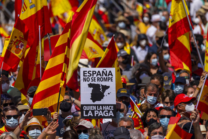 """Thousands gather during a protest against the Spanish government's plan to issue pardons to a dozen imprisoned Catalan separatist leaders, Madrid, Sunday, 13 June, 2021. The demonstration has been organized by a civil society group in defense of the nation's unity that chose to hold it at a central square that has become popular for far-right political rallies. The banner reads in Spanish """"You can't break Spain. Whoever does it, will pay for it."""". (AP Photo/Bernat Armangue)"""