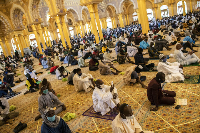 In this photo taken Friday, May 15, 2020, a follower of the Senegalese Mouride brotherhood, an order of Sufi Islam, films with his smartphone as he and others practice social distancing as they attend Muslim Friday prayers at West Africa's largest mosque the Massalikul Jinaan, in Dakar, Senegal. A growing number of mosques are reopening across West Africa even as confirmed coronavirus cases soar, as governments find it increasingly difficult to keep them closed during the holy month of Ramadan. (AP Photo/Sylvain Cherkaoui)