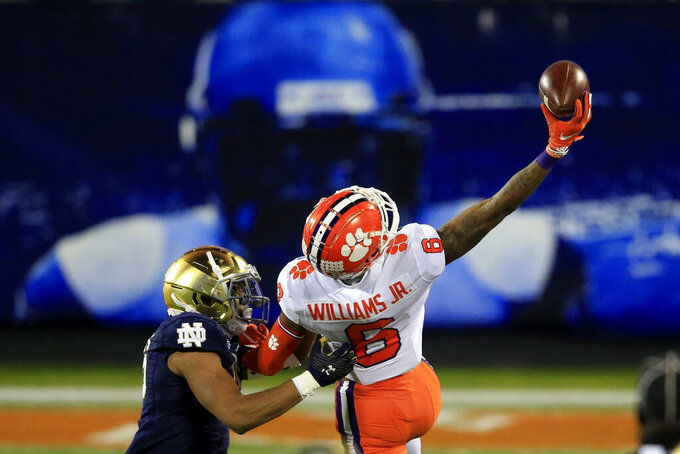 Clemson wide receiver E.J. Williams (6) hauls in a pass with one hand in front of Notre Dame cornerback Clarence Lewis (26) for a gain of 22-yards during the second half of the Atlantic Coast Conference championship NCAA college football game, Saturday, Dec. 19, 2020, in Charlotte, N.C. (AP Photo/Brian Blanco)