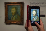 A journalist takes a picture of the previously contested painting by Dutch master Vincent van Gogh, a 1889 self-portrait, of which the authenticity was confirmed during a press conference in Amsterdam, Netherlands, Monday, Jan. 20, 2020. The painting, which belongs to the National Museum in Norway, was painted at the Saint-Paul de Mausole psychiatric institution in Saint-Remy de Provence, France. (AP Photo/Peter Dejong)