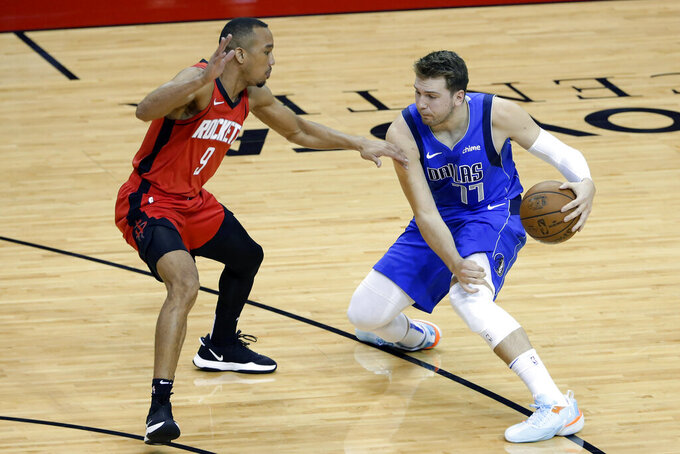 Dallas Mavericks guard Luka Doncic (77) works to drive around Houston Rockets guard Avery Bradley (9) during the first half of an NBA basketball game Wednesday, April 7, 2021, in Houston. (AP Photo/Michael Wyke, Pool)