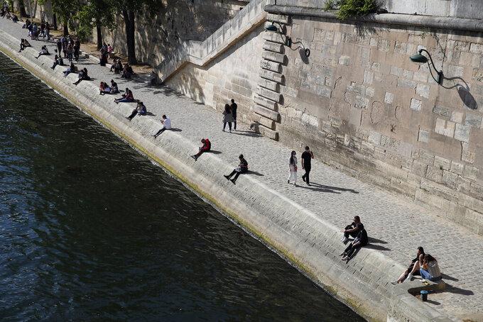 Parisians sit in the sun along the Seine river banks in Paris, Saturday, May 23, 2020 as France gradually lifts its COVID-19 lockdown. (AP Photo/Francois Mori)