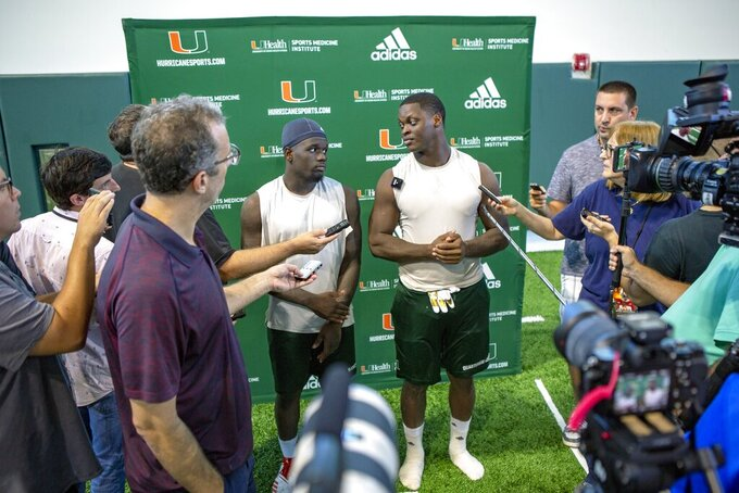 University of Miami cornerback Trajan Bandy (2), left, and linebacker Shaq Quarterman (55), right, speak to the media after morning practice before Saturday night's ACC opener at North Carolina, at the Carol Soffer Indoor Practice Facility in Coral Gables, Florida on Wednesday, September 4, 2019.(Daniel A. Varela/Miami Herald via AP)