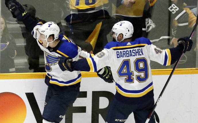 """FILE - In this Feb. 10, 2019 file photo, St. Louis Blues right wing Vladimir Tarasenko, of Russia, left, celebrates with Ivan Barbashev (49), of Russia, after Tarasenko scored the winning goal in overtime against the Nashville Predators in an NHL hockey game in Nashville, Tenn. More than two decades since Fetisov and the """"Russian Five"""" shattered the myth that NHL teams couldn't win with players from a nation unpopular in North America, Tarasenko and Barbashev are one victory away from lifting the same Cup after being inspired by the generation of countrymen who endured so much to get there. (AP Photo/Mark Humphrey, File)"""