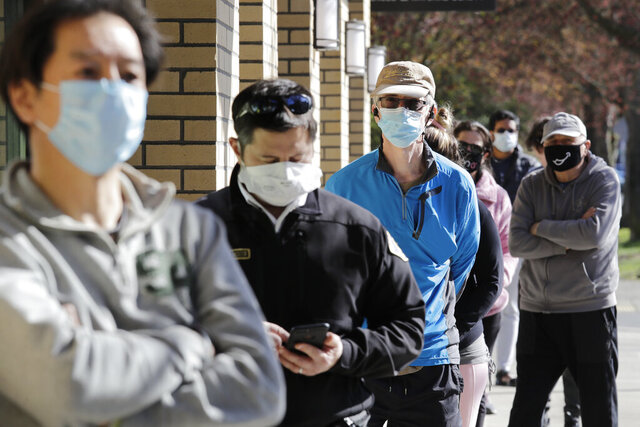 Customers wear a variety of protective masks as they wait some six-feet apart to enter a Trader Joe's store, where the number of customers allowed inside at any one time was limited because of the coronavirus outbreak, Wednesday, April 8, 2020, in Seattle. (AP Photo/Elaine Thompson)