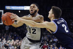 Providence guard Luwane Pipkins (12) secures a loose ball against Villanova guard Collin Gillespie (2) in the second half of an NCAA college basketball game, Saturday, Jan. 25, 2020, in Providence, R.I. Villanova won, 64-60. (AP Photo/Elise Amendola)