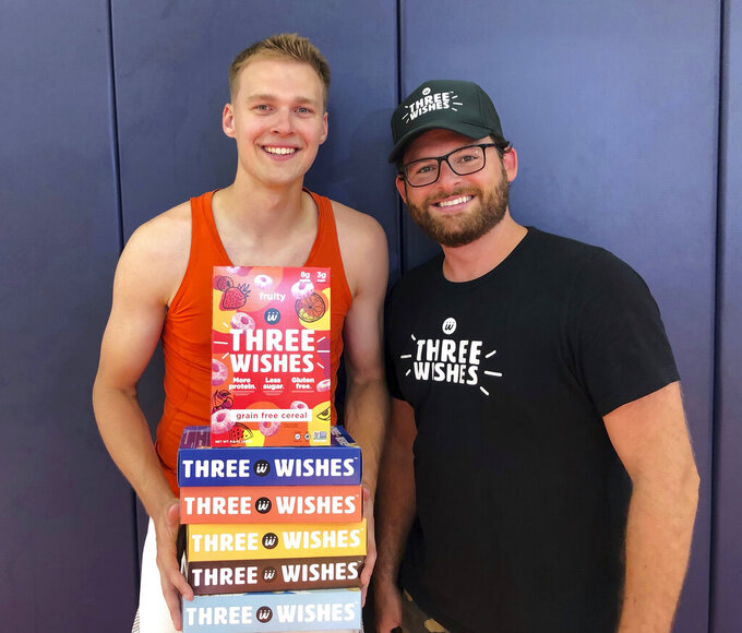 In this image provided by Three Wishes Foods, Syracuse's Buddy Boeheim, left, poses with Three Wishes Foods co-founder Ian Wishingrad on Wednesday, July 14, 2021, in DeWitt, N.Y. A new era in college sports got underway at the beginning of July, and with players now allowed to make money on their celebrity it's anybody's guess where this is all headed. Boeheim, the sharp-shooting son of Syracuse men's basketball coach Jim Boeheim, inked a deal that will put his likeness on the front of a cereal box with him shooting, a morsel of Three Wishes cereal in his right palm. . (Scott Yager/Three Wishes Foods via AP)