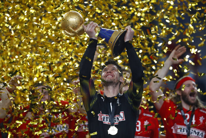 Denmark's players celebrate with the trophy after the World Handball Championship final game against Sweden in Cairo, Egypt, Sunday, Jan. 31, 2021. (AP Photo/Petr David Josek)