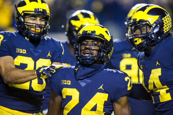 Michigan defensive back Lavert Hill (24) celebrates his touchdown interception with defensive backs Brandon Watson, left, and Josh Metellus during the fourth quarter of an NCAA college football game against Wisconsin in Ann Arbor, Mich., Saturday, Oct. 13, 2018. Michigan won 38-13. (AP Photo/Tony Ding)