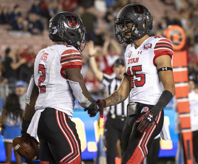 Utah running back Zack Moss, left, celebrates his touchdown with wide receiver Samson Nacua during the second half of an NCAA college football game against UCLA Friday, Oct. 26, 2018, in Pasadena, Calif. (AP Photo/Kyusung Gong)