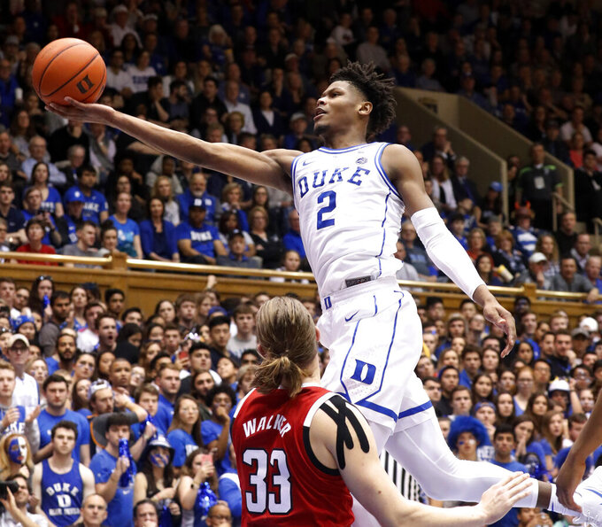 FILE - In this Feb. 16, 2019, file photo, Duke's Cam Reddish (2) drives to the hoop against North Carolina State's Wyatt Walker (33) during the second half of an NCAA college basketball game, in Durham, N.C. Duke has reclaimed the No. 1 spot in the AP Top 25 college basketball poll. The Blue Devils earned 58 of 64 first-place votes in Monday's, Feb. 18, 2019, poll to earn a third stint at the top this season. (AP Photo/Chris Seward, File)