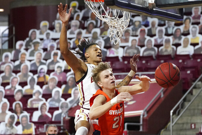 Boston College guard Makai Ashton-Langford (4) blocks a shot by Syracuse forward Marek Dolezaj (21) during the first half of an NCAA college basketball game, Saturday, Dec. 12, 2020, in Boston. (AP Photo/Elise Amendola)