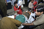 Volunteers rush a wounded police officer to a hospital in Lahore, Pakistan, Wednesday, March 14, 2018. A suspected suicide bombing near a police checkpoint killed several police and bystanders, and wounded more than 20 others on Wednesday near the city of Lahore in eastern Pakistan, police said. (AP Photo/K.M. Chaudary)